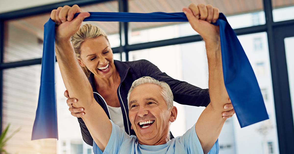 Man holding resistance band above head with physical therapist behind him