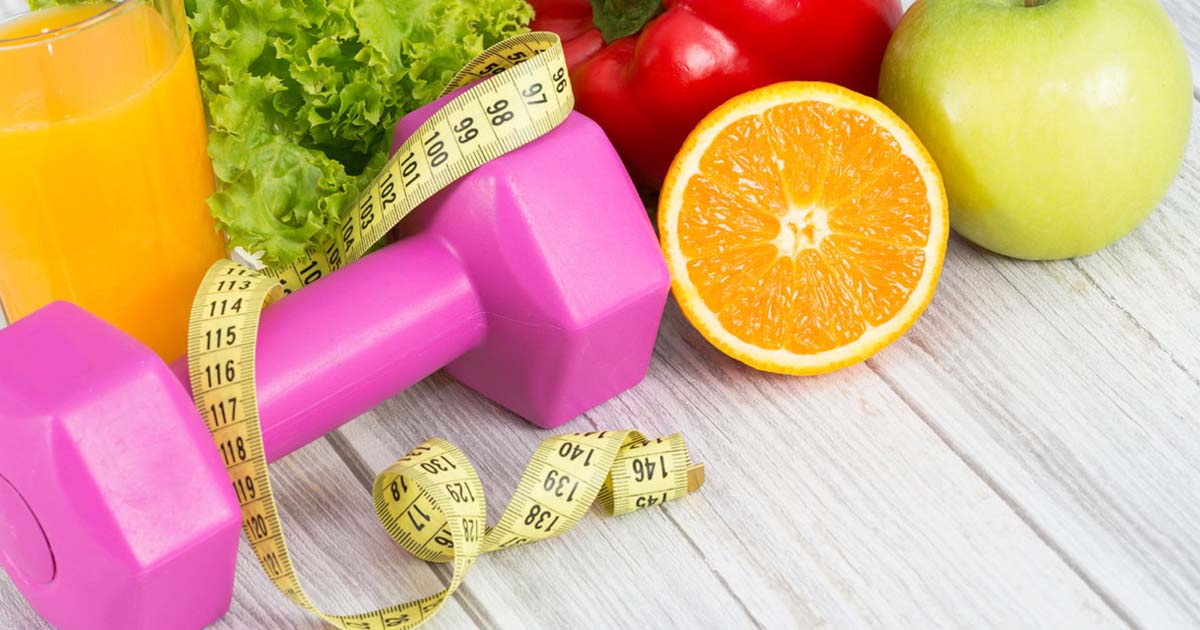 Healthy vegetables and fruits, a pink hand-weight, and body measuring tape