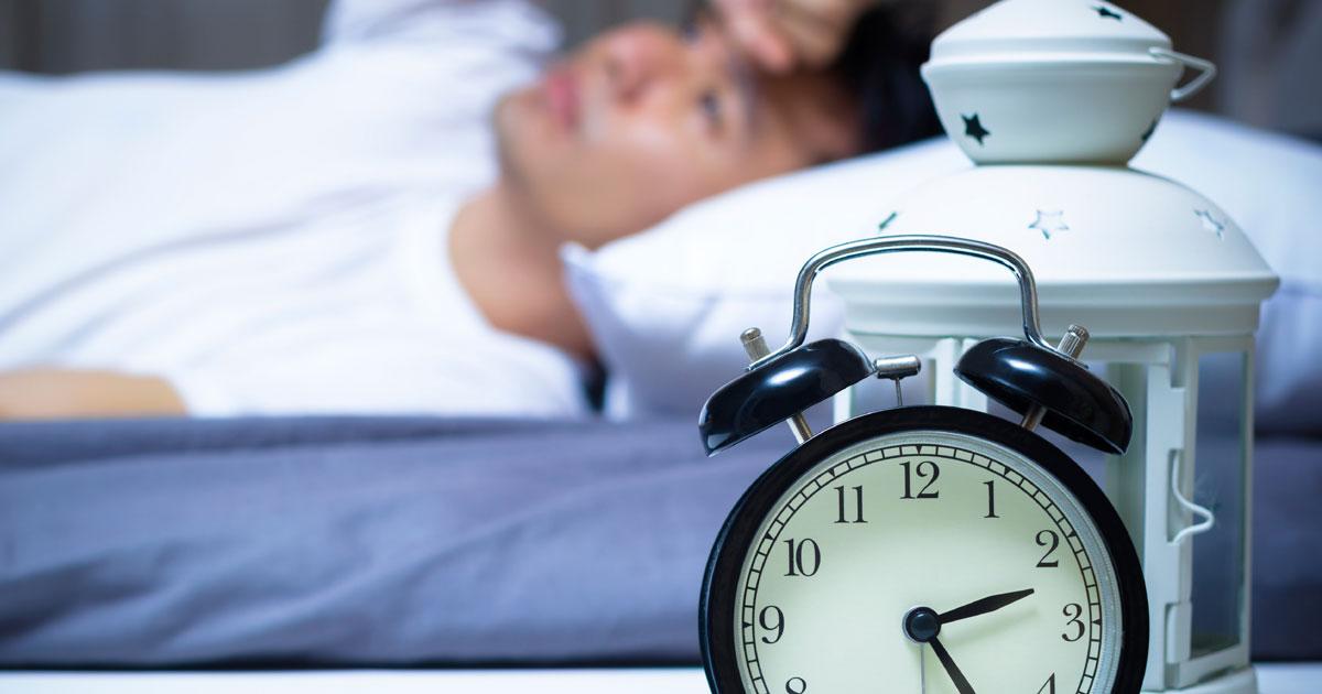 Man laying in bed wide-awake