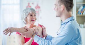 Physical therapist helping older woman stretch her arm across her body