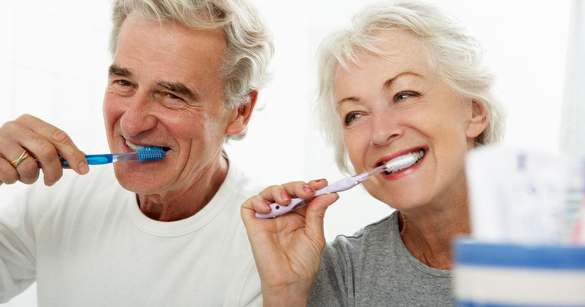Husband and wife brushing teeth together
