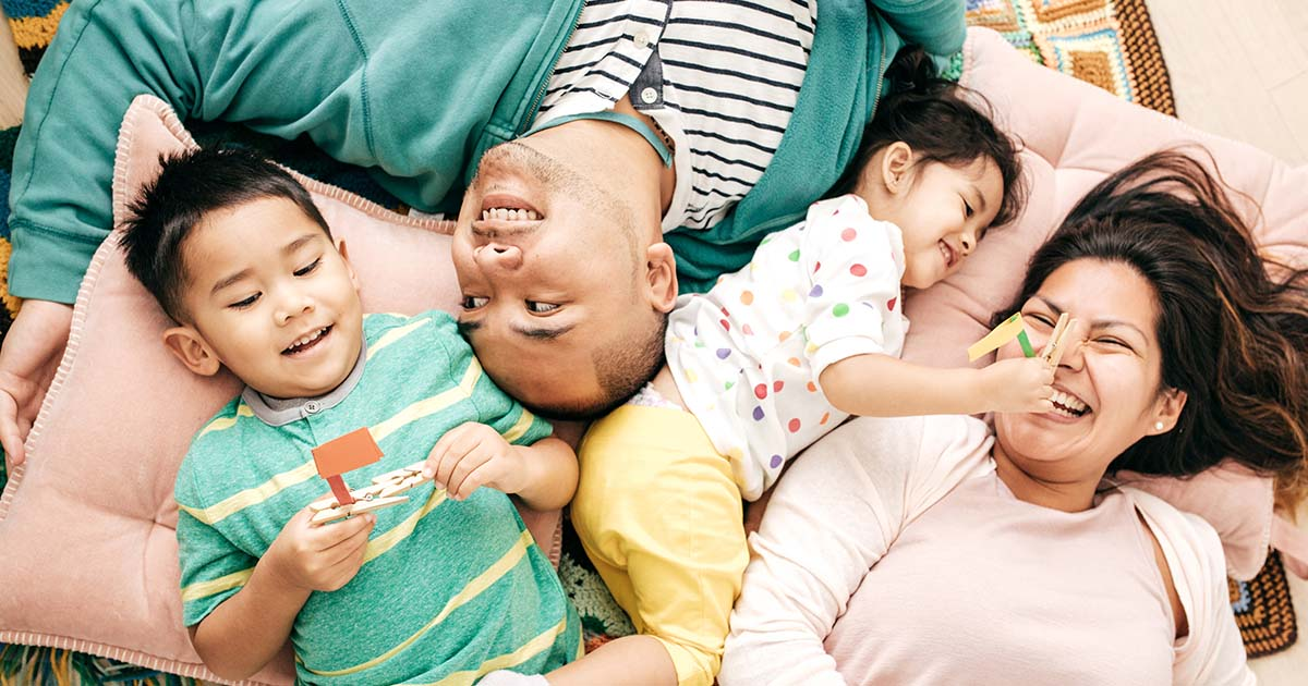Parents and two kids lying on bed together laughing