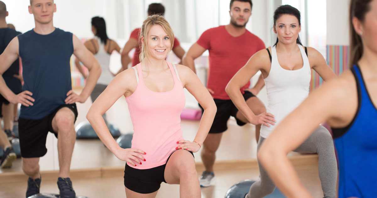 Women and men doing lunges in a fitness class