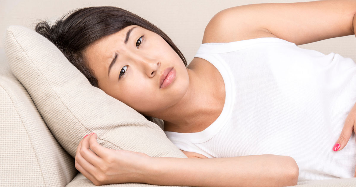 Woman lying on couch looking concerned