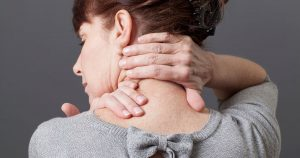 Woman holding the back of her neck with both hands