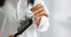 Woman pulling hair out of hair brush