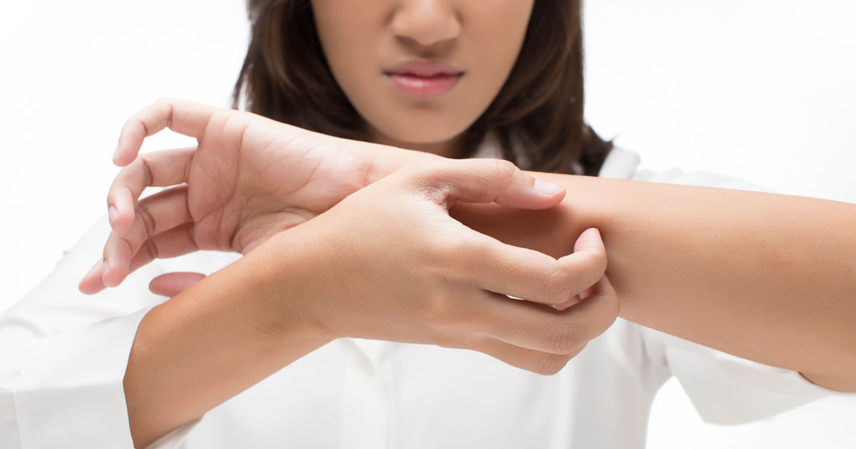 Woman itching her forearm