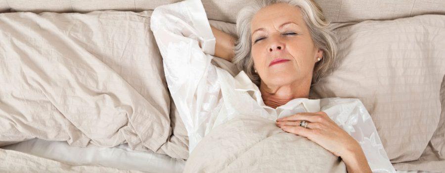 Older woman lying awake in bed