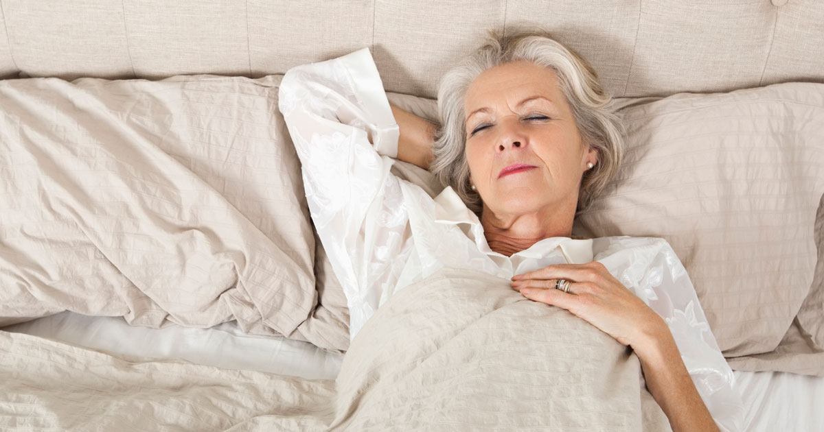 Older woman lying awake in bed