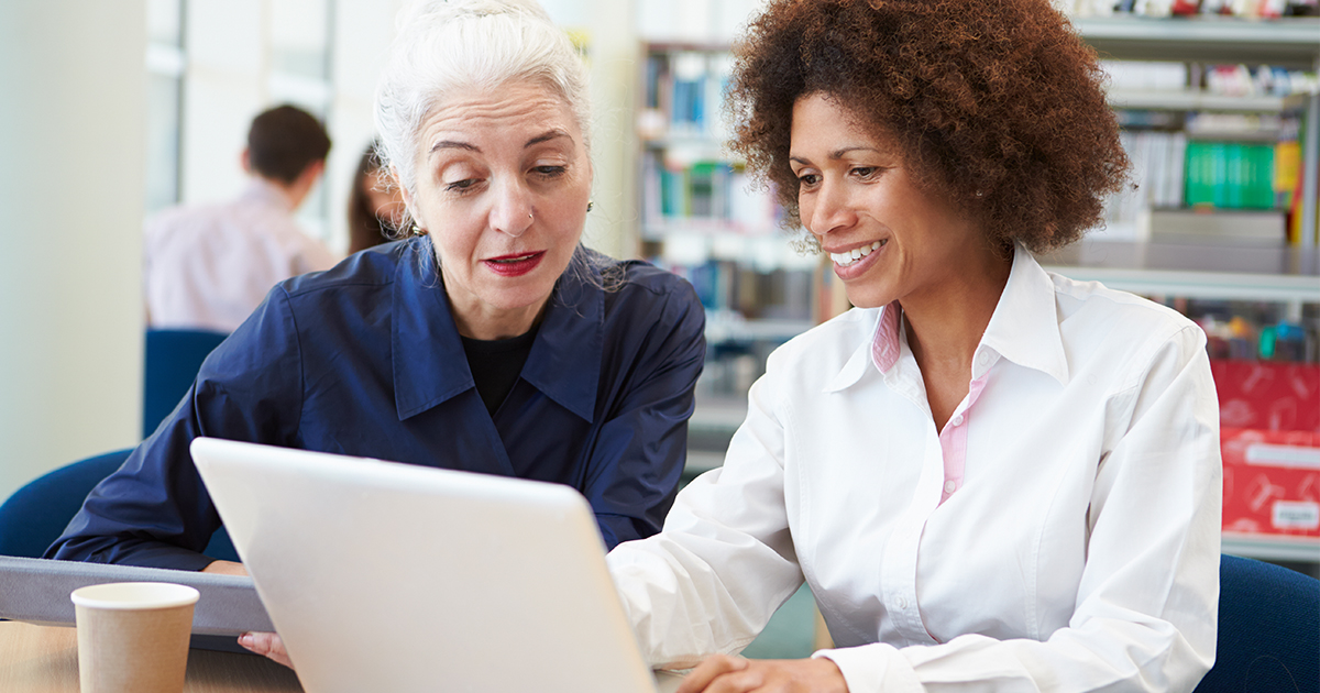 Woman teaching another woman how to use a computer