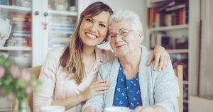 Woman with her arms around her grandmother