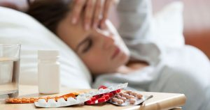Woman lying in bed holding head with empty pill packages on bedside table.