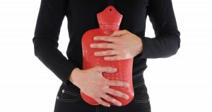 Person holding hot water bottle against stomach