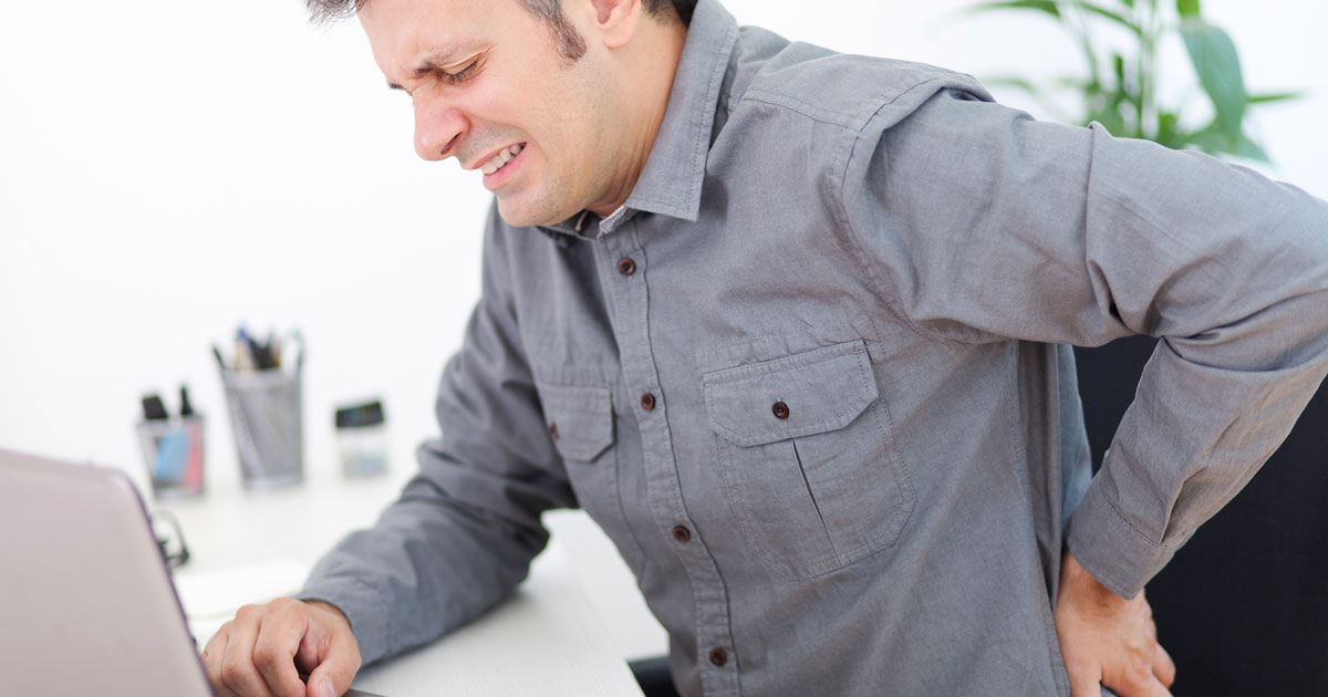 Man sitting at desk, with one hand on lower back, face in pain
