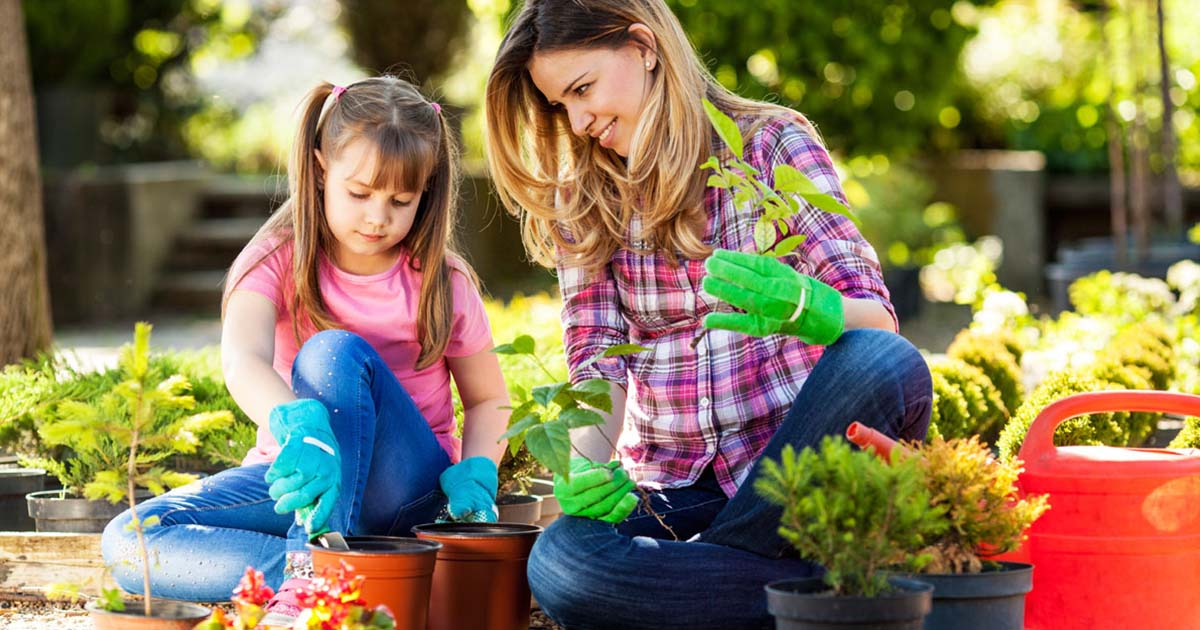 Mom and daughter planting plants in the garden