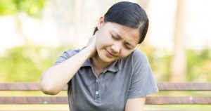 Woman sitting outside with hand rubbing back of neck