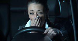 Yawning woman behind the steering wheel