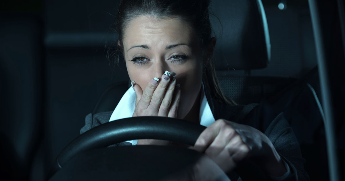 Yawning woman behind the steering wheel