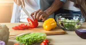 Man cutting vegetables for healthy vegetarian salad in kitchen