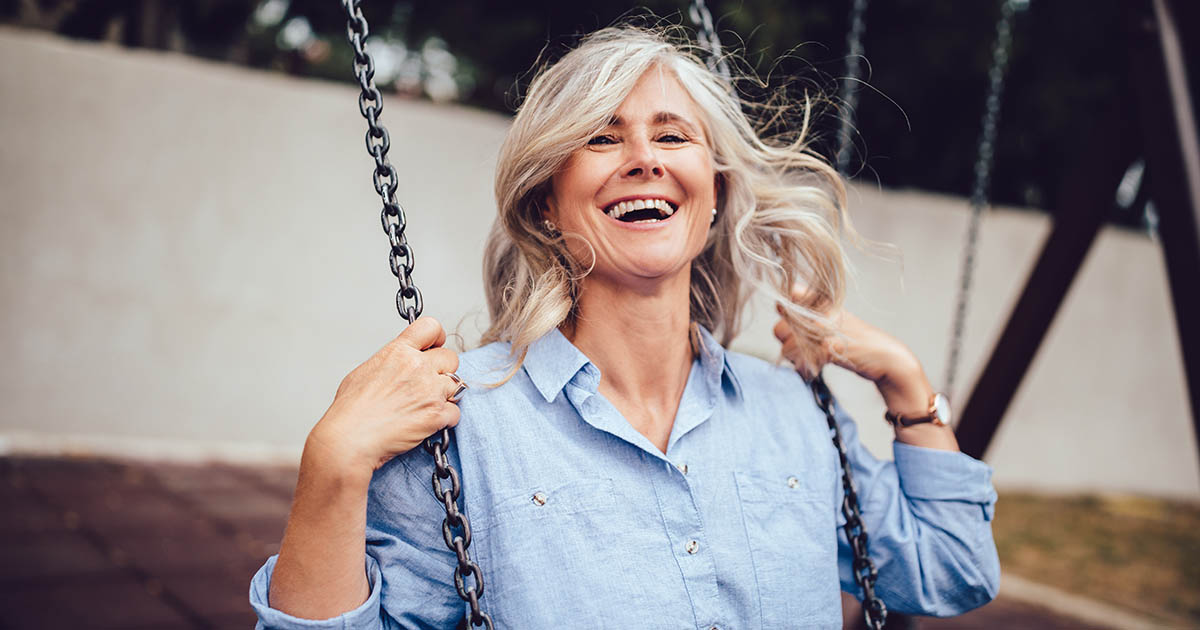 Mature woman with gray hair sitting on swing and having fun
