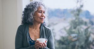 Woman drinks tea by window while contemplating