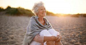 Older woman sitting on beach