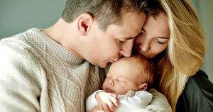 Mother and father kissing head of newborn baby