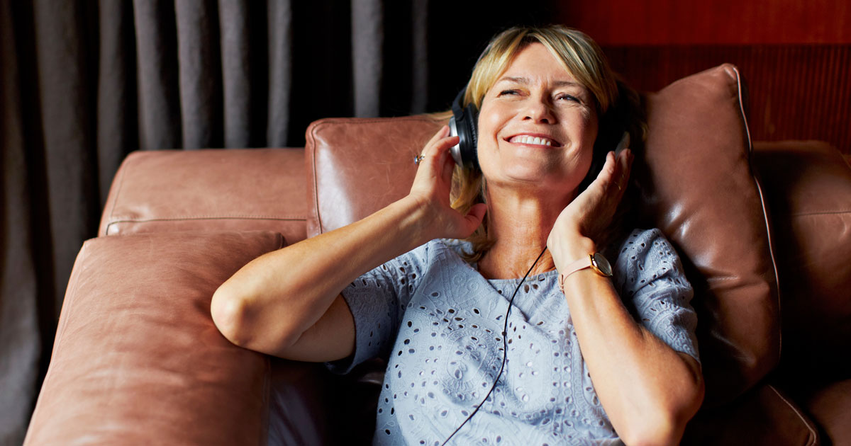 Woman wearing headphones and sitting on a couch