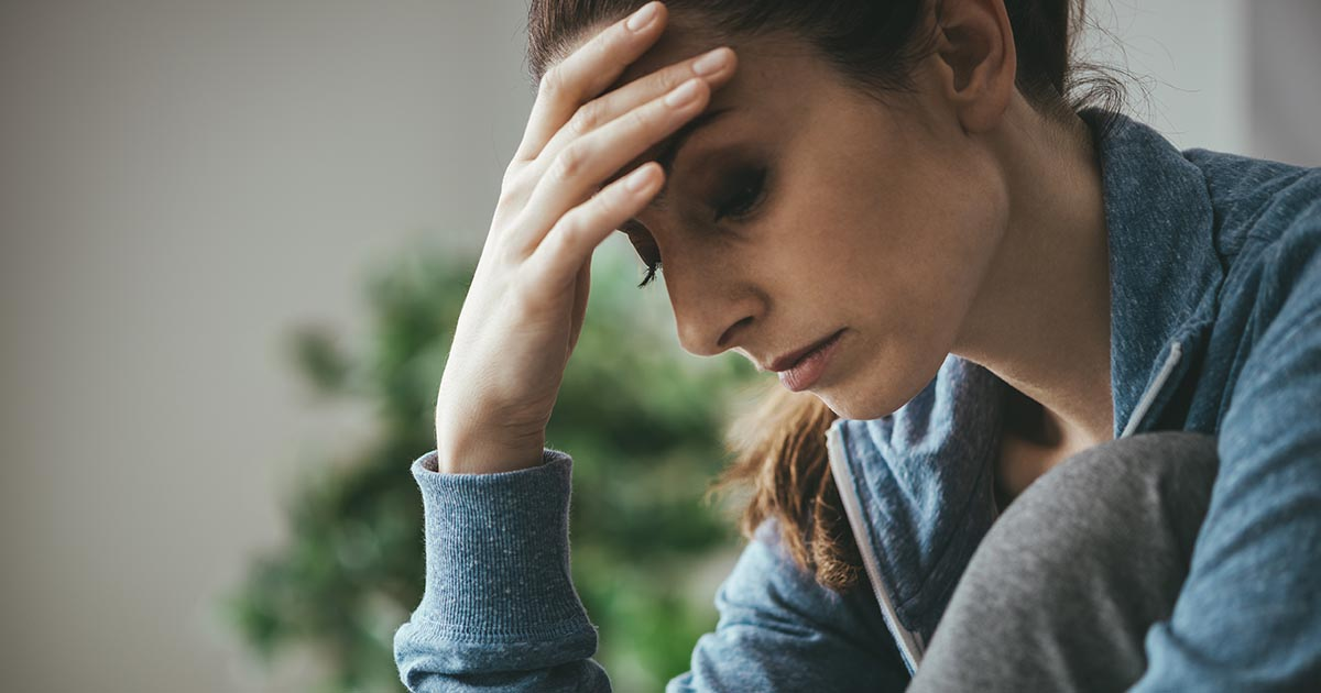 Woman with hand to forehead looking upset