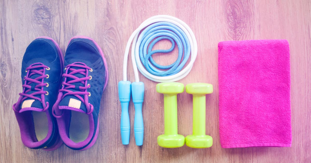 Running shoes, skipping rope, weights and sweat towel on ground