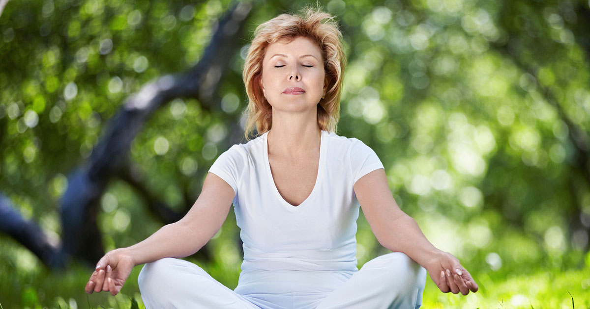 Woman sitting outside, meditating