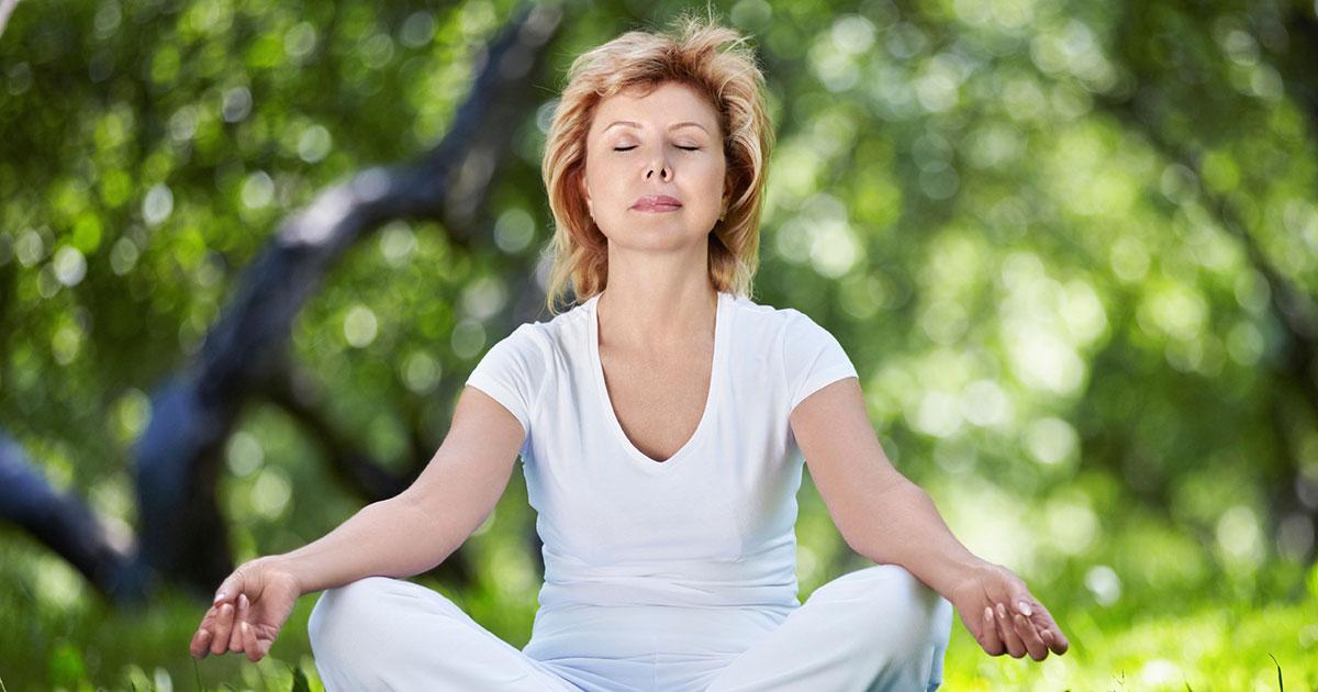 Woman sitting outside, meditating