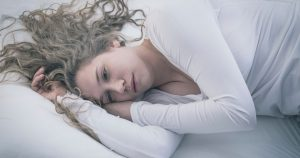 Woman lying on bed awake