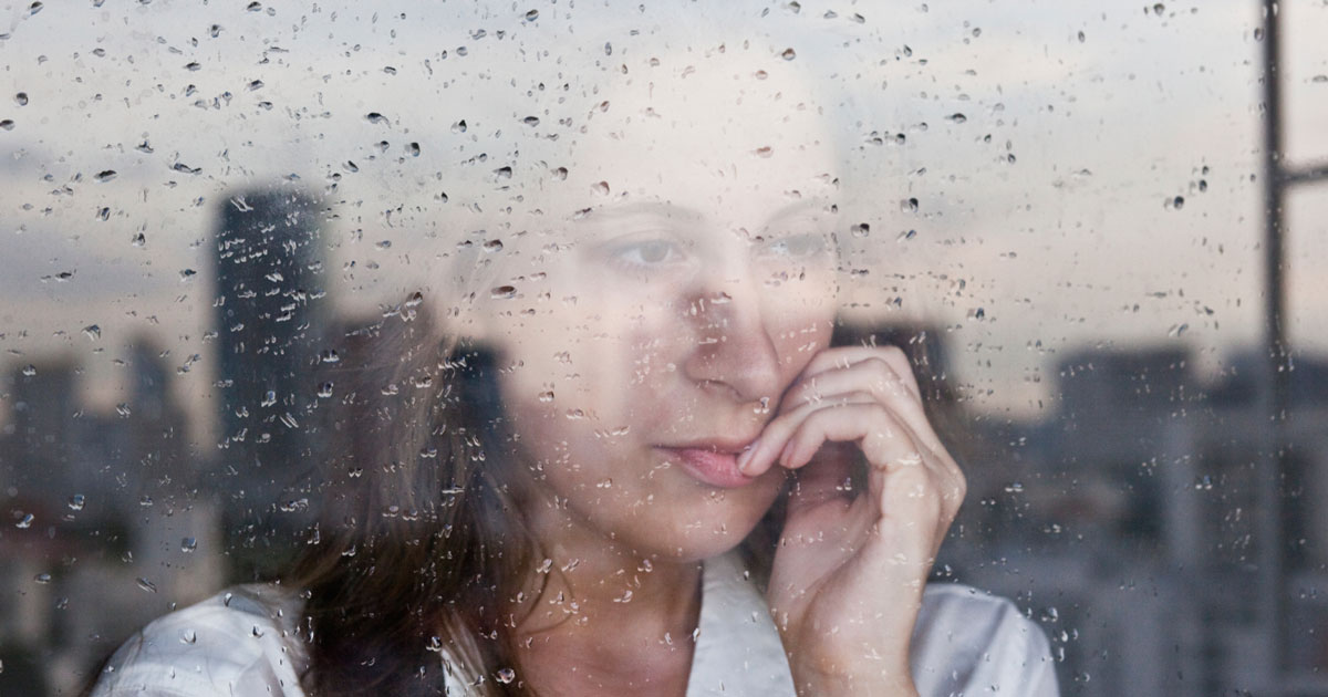 Woman staring out window looking concerned