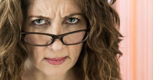 Woman wearing glasses and frowning