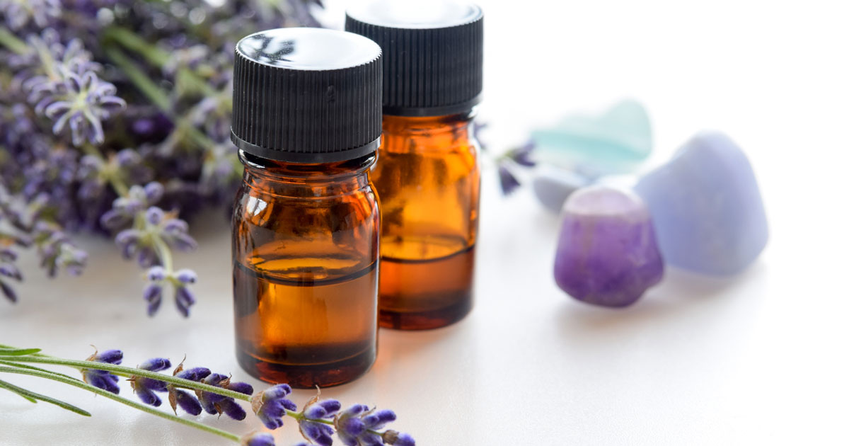 Two bottles of essential oil with lavender sprigs beside