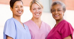 Three female nurses wearing scrubs