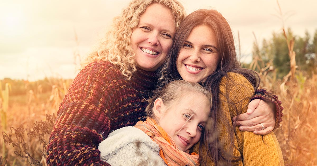 Mother with arms around her two daughter