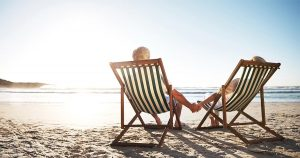Two people sitting in lounge chairs on the beach