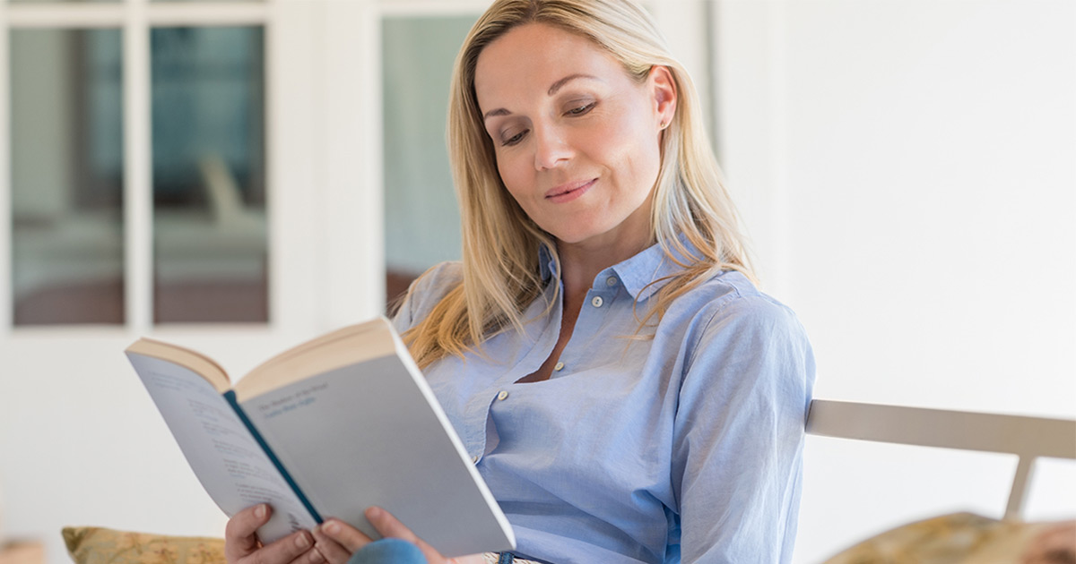 Woman sitting inside reading a book