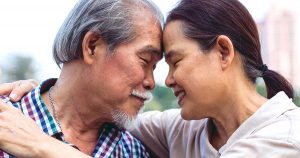 Older man and woman with foreheads pressed together
