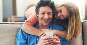 Man sitting on couch looking at phone with woman leaning over couch behind him with arms around him