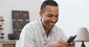 Man smiling as he reads something on his phone