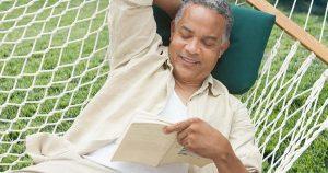 Man lying in a hammock reading a book