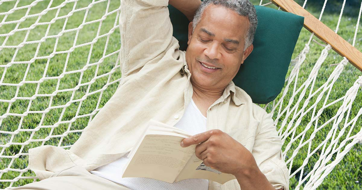 Man lying in a hammock reading a book