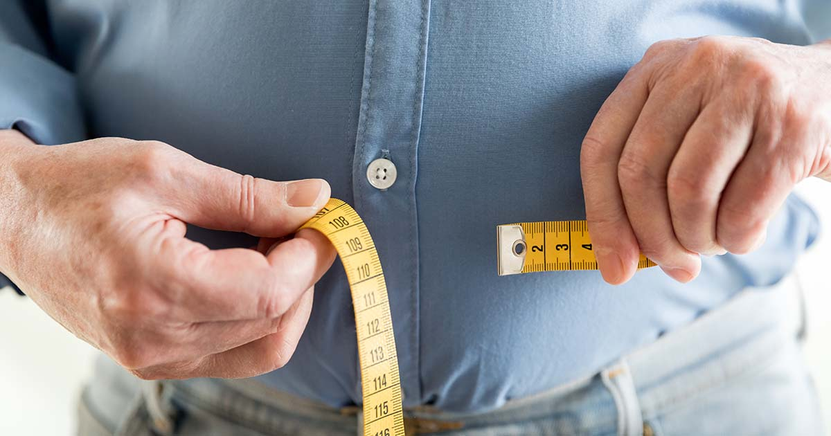 Man holding a measuring tape around his stomach