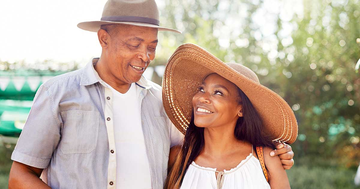 Man and woman with arms around each other, wearing sun hats