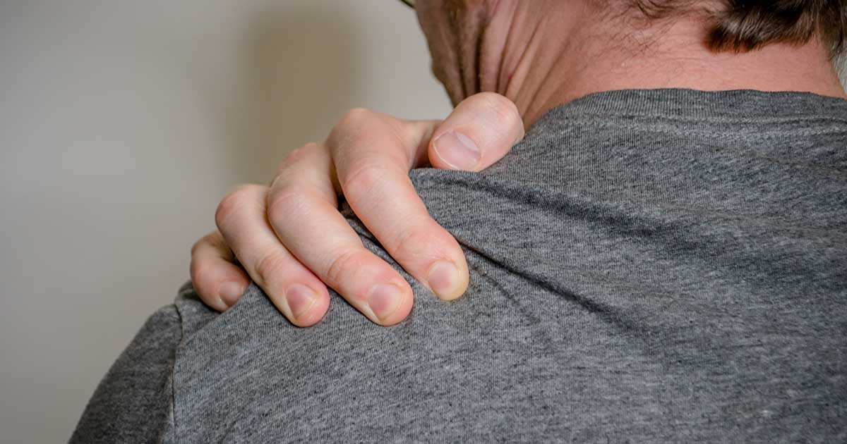 Man gripping his shoulder in pain