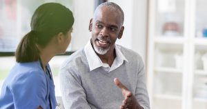 A young nurse listens as a senior man talks and gestures in a medical office.