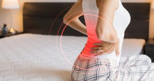 a woman holding her back due to fibromyalgia pain